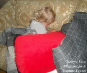 boy covered with pillows